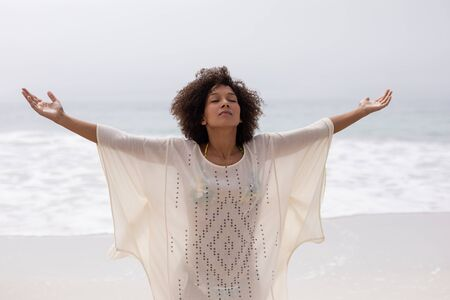 Front view of African american woman standing with arms outstretched on the beach