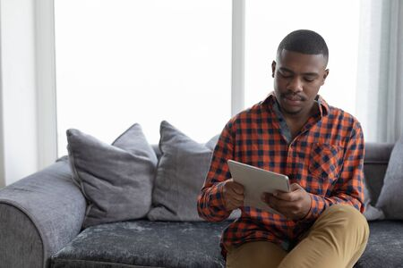 Front view of African american man using digital tablet on a sofa in living room at home