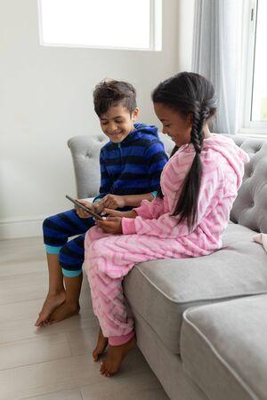 Vista lateral de los hermanos felices afroamericanos con tableta digital en un sofá en la sala de estar en casa