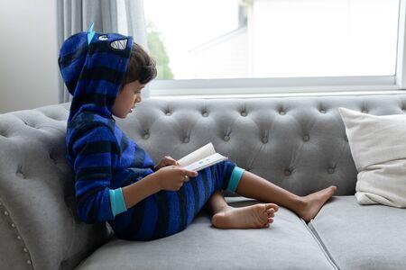 Vista lateral del niño afroamericano leyendo un libro en un sofá en la sala de estar en casa