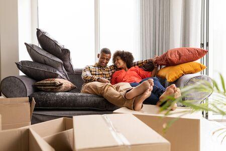 Vorderansicht eines glücklichen gemischtrassigen Paares, das zusammen auf einem Sofa sitzt, mit den Füßen auf den Kartons im Wohnzimmer zu Hause Standard-Bild