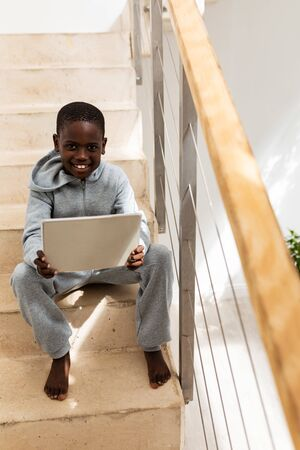 Front view of African american boy using digital tablet on staircase at home 免版税图像