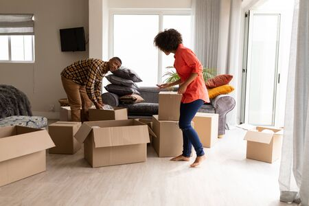 Front view of happy mixed-race couple unpacking cardboard boxes in living room at home. Stock Photo