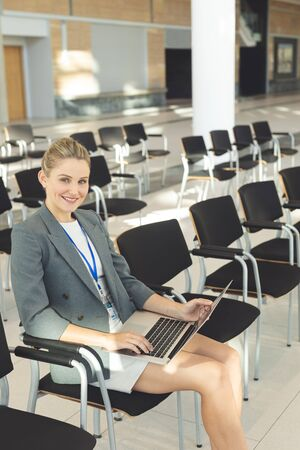 Side view of young businesswoman sat in empty conference room with laptop, smiling at camera