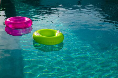 Inflatable tubes floating in a swimming pool in backyard at home