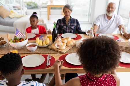 Over the shoulder view of happy mixed-race multi-generation family praying before having meal on dining table at home. They are holding hands and having their eyes closed.