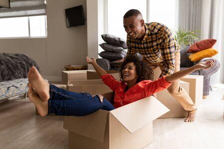 Vista lateral de la feliz pareja afroamericana divirtiéndose juntos en la sala de estar en casa
