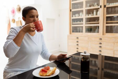 Side view of African american Woman using mobile phone while having coffee on a dining table at kitchen