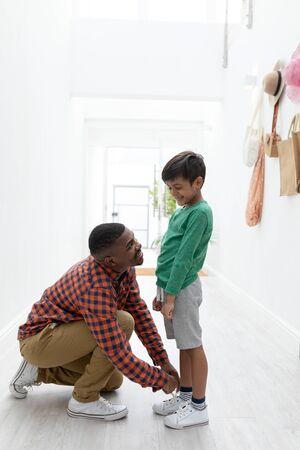 Seitenansicht des afroamerikanischen Vaters, der seine Söhne beim Schnüren zu Hause bindet Standard-Bild