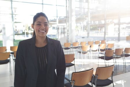 Front view of smiling mixed-race businesswoman standing in empty conference room