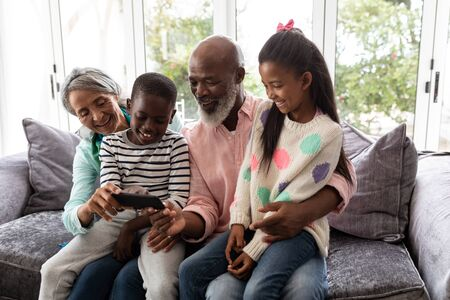 Front view of African american Multi-generation family looking at photos on mobile phone in living room at home Фото со стока