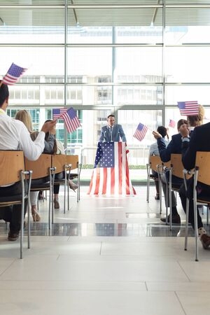 Rear view of group of diverse business people with flags listening mature Caucasian businessman presentation