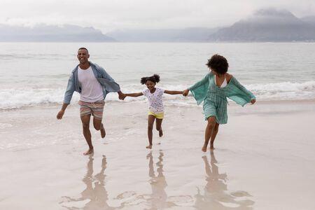 해변에서 함께 즐거운 시간을 보내는 행복한 아프리카계 미국인 가족의 전면 모습