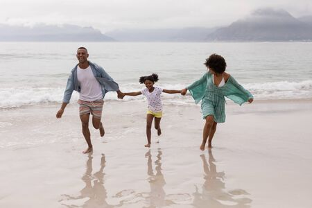 Vue de face d'une famille afro-américaine heureuse s'amusant ensemble sur la plage