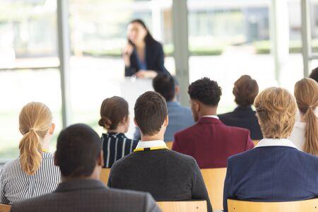 Vooraanzicht van jonge Aziatische vrouwelijke stafmedewerker die toespraak in conferentieruimte doet