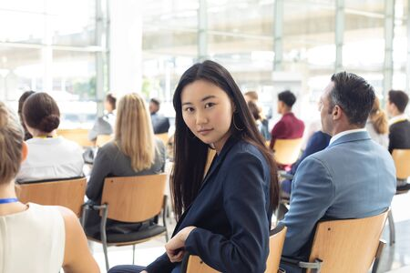 Side view of young Asian businesswoman sat in conference room, smiling to camera