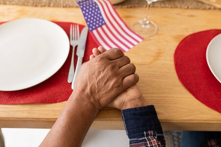 Close-up of senior mixed-race couple praying with hand in hand on dining table at home