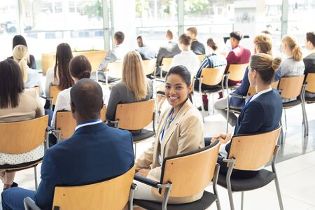 Side view of young mixed race female executive sat in conference room, smiling to camera