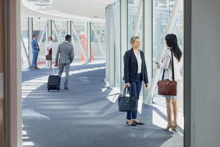 Side view of businesswomen interacting with each other in corridor in modern office