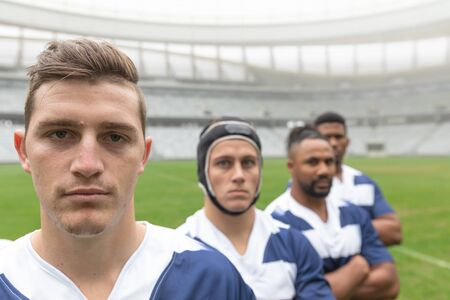 Portrait of diverse male rugby players standing together in stadium