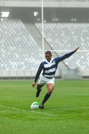 Front view of African American male rugby player kicking rugby ball in stadium