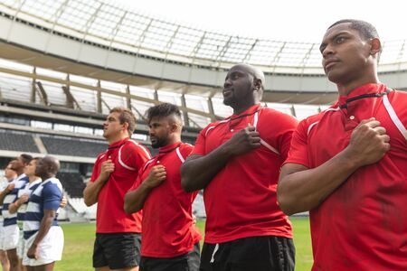 Front view of proud diverse rugby team taking pledge together in stadium Stock Photo