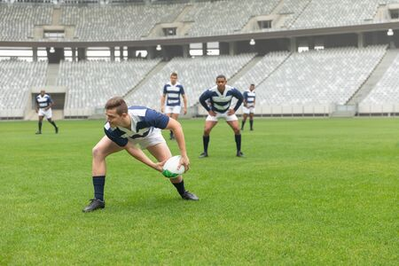 Side view of group of diverse male rugby players playing rugby match in stadium