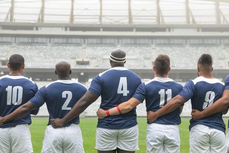 Rear view of group of diverse male rugby players taking pledge together in stadium Archivio Fotografico