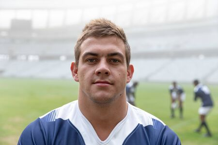 Portrait of Caucasian Male rugby player standing in stadium. with players in the background Stock Photo
