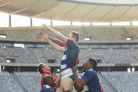 Side view of diverse male rugby players trying to catch the ball in the air while team members hold them in the air in stadium on sunny day.