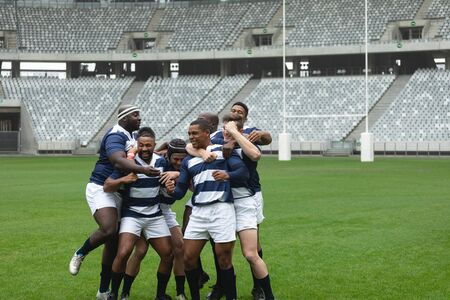 Side view of group of diverse male rugby players celebrating goal in stadium Stock Photo