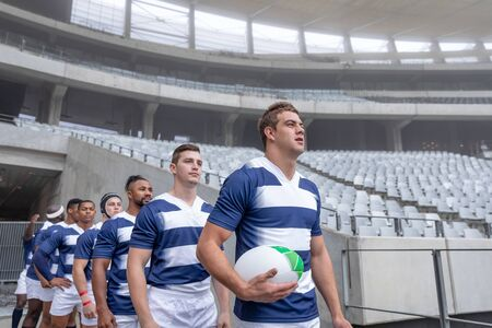 Side View of group of diverse rugby players entering stadium in a row for match Stock Photo