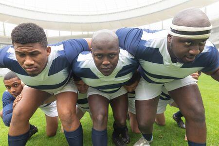 Vorderansicht der Gruppe verschiedener männlicher Rugbyspieler, die bereit sind, ein Rugbyspiel im Stadion zu spielen