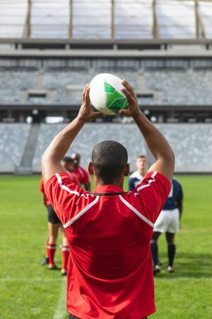 Rear view of handsome African American male rugby player throwing rugby ball in stadium. Diverse players are waiting on player to throw the ball.