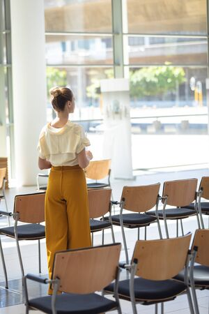 Rear view of young Caucasian female executive looking away while standing in empty conference room 免版税图像