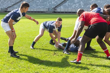 Front view of Caucasian male rugby player getting the ball from African American male rugby player who is lying on the ground while diverse team surround them in stadium on sunny day. Stock Photo