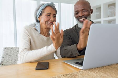 Front view of diverse senior couple video chatting using laptop in beach house. They are waving. Authentic Senior Retired Life Concept