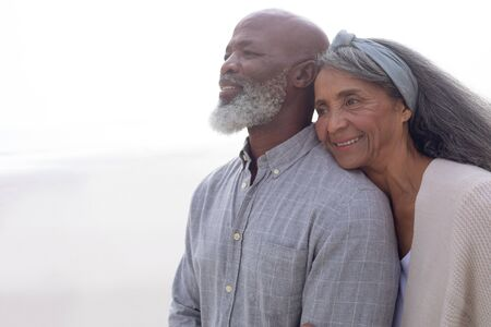 Portrait of happy senior African-American couple standing on the beach on cloudy day. Authentic Senior Retired Life Concept
