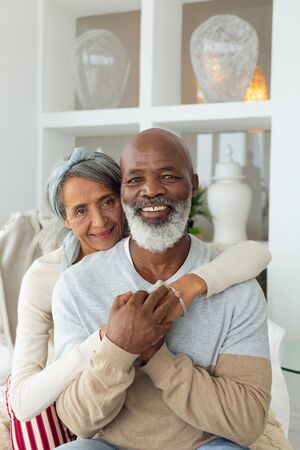 Front view of happy senior diverse couple sitting inside a room smiling to the camera in beach house. Authentic Senior Retired Life Concept