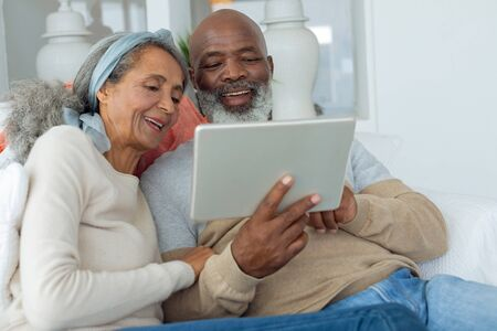 Front view of diverse senior couple using a digital tablet on sofa in beach house. Authentic Senior Retired Life Concept