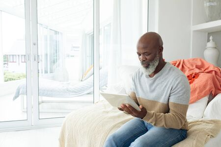 Front view of handsome senior African american man using a digital tablet on sofa in beach house. Authentic Senior Retired Life Concept
