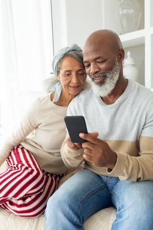 Front view of diverse couple using a smartphone on sofa. Authentic Senior Retired Life Concept Banque d'images