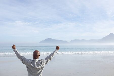 Rear view of handsome senior African-American man with arms spread standing on beach on beautiful day. Authentic Senior Retired Life Concept