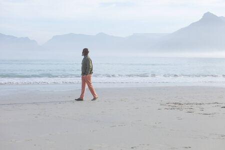 Vista lateral del apuesto hombre afroamericano senior caminando por la playa con las manos en los bolsillos en un hermoso día. Auténtico concepto de vida jubilado senior Foto de archivo