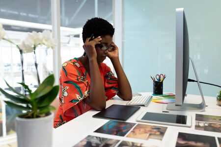 Side view of young African american female graphic designer sitting at desk in office. This is a casual creative start-up business office for a diverse team