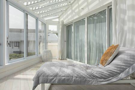 Seitenansicht einer großen modernen Veranda mit Bett