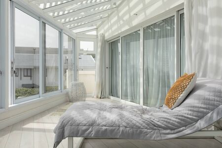 Side view of a large modern veranda with a bed