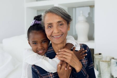 Portrait close up of African american girl and mixed race grandmother sitting on bed. Authentic Senior Retired Life Concept