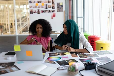 Front view of diverse female graphic designers discussing over laptop at desk in office. This is a casual creative start-up business office for a diverse team