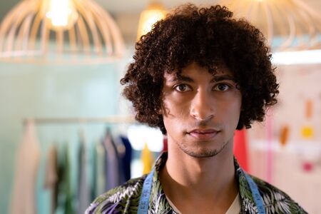 Portrait of young mixed race male fashion designer standing in design studio. This is a casual creative start-up business office for a diverse team 스톡 콘텐츠